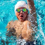 Young swimmer with cap and goggles.