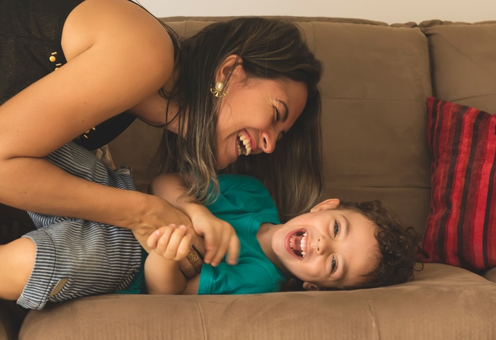 Mother and her child, tickling, kidding and having fun in the couch, with spontaneous smiles.