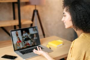 woman, laptop. viewing Zoom meeting