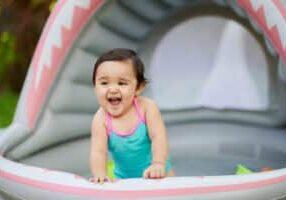 Funny baby girl in swimming kid pool in house garden
