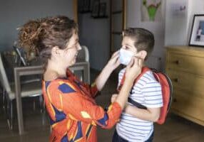 Mother putting a face mask to her son. Focus on child