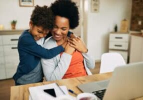 Happy working black mother and her small son embracing at home.