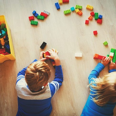 little boy and girl play with plastic blocks, kids learning activities